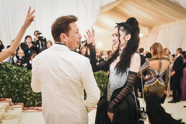 Elon Musk and Grimes, he from behind, she in profile, on the red carpet for the Met Gala in 2018.