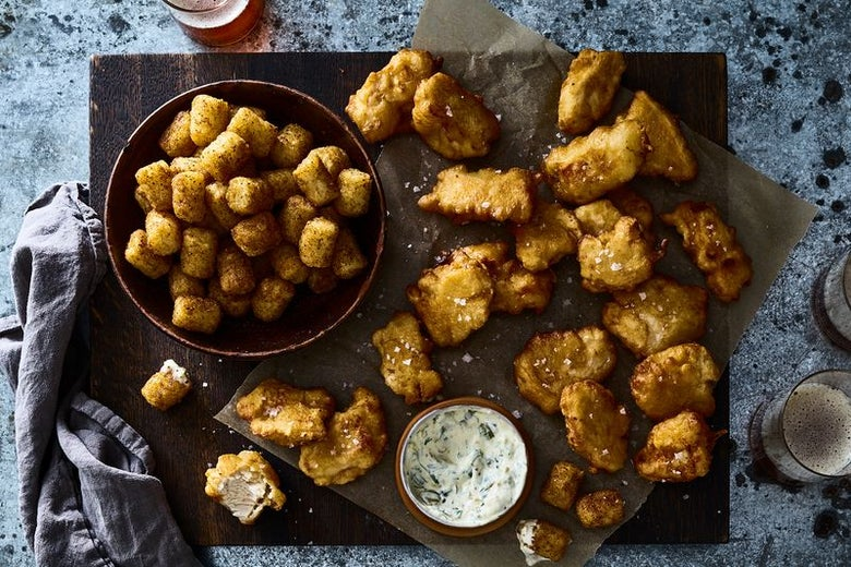 A bowl of tater tots sits next to a wooden board laden with chicken nuggets. There is a bowl of white dipping sauce on the board. One of the nuggets has a bite out of it.