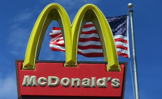 A sign for a McDonald's restaurant sits in front of an American Flag.