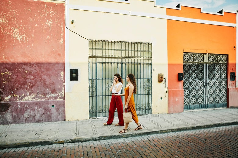 Two women walking down a brightly painted street.