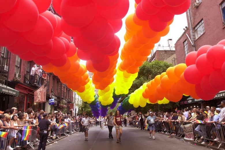 Rainbow balloons over a street during a Pride parade.