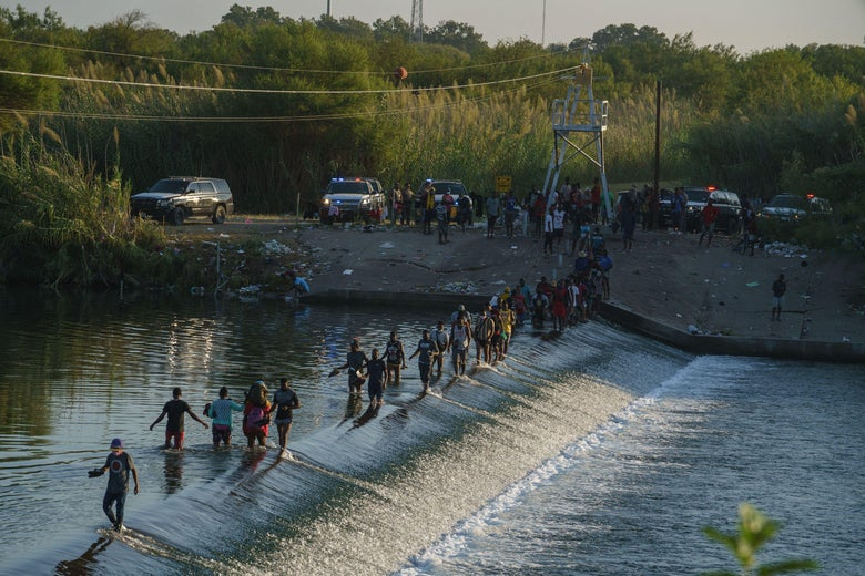 Haitian migrants cross the Rio Grande to get food and supplies near the Del Rio-Acuña Port of Entry in Ciudad Acuña, Coahuila state, Mexico on September 18, 2021.