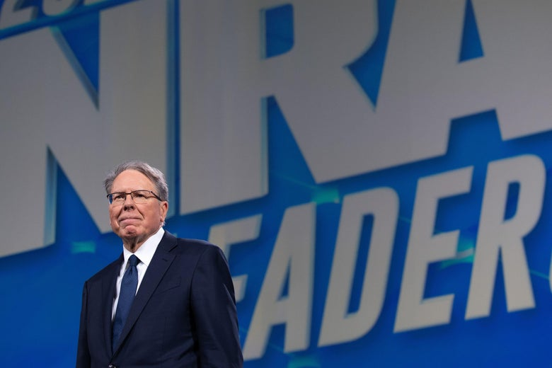 LaPierre standing in front of an NRA banner