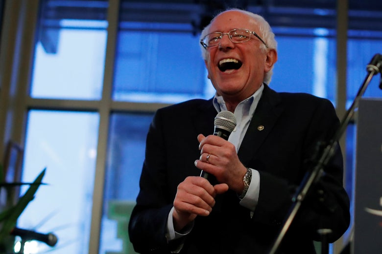 Bernie Sanders laughing while holding a mic