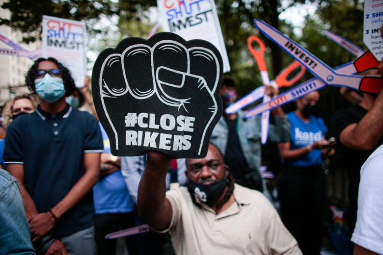 """A Black man holds up a black foam fist that says, """"#CloseRikers."""""""