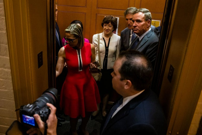 The four senators stand in an elevator as Sinema presses a button.
