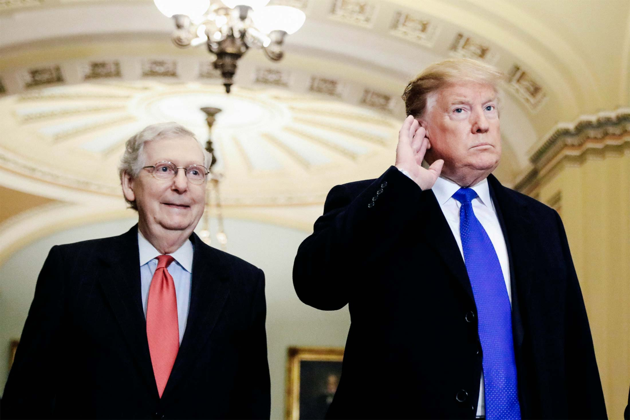 President Donald Trump listens to questions from reporters next to Senate Majority Leader Mitch McConnell.