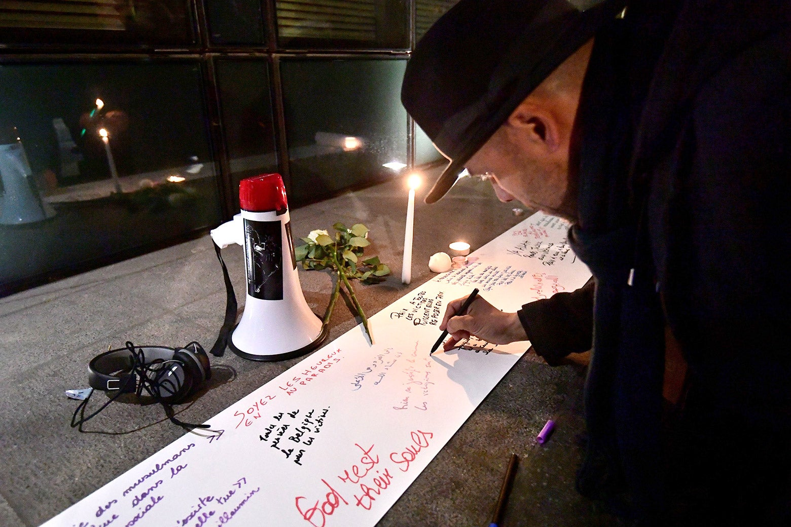 A man writes on a white sheet. There are candles.