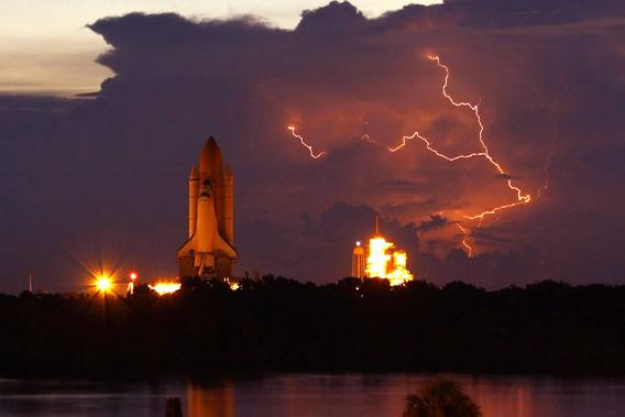The space shuttle Discovery rolls out to Launch Pad 39A with lightning in the area at NASA's Kennedy Space Center in Cape Canaveral, Florida.