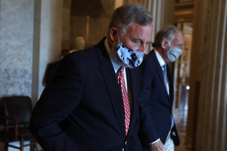 Burr walking with his eyes down, face covered by a mask.
