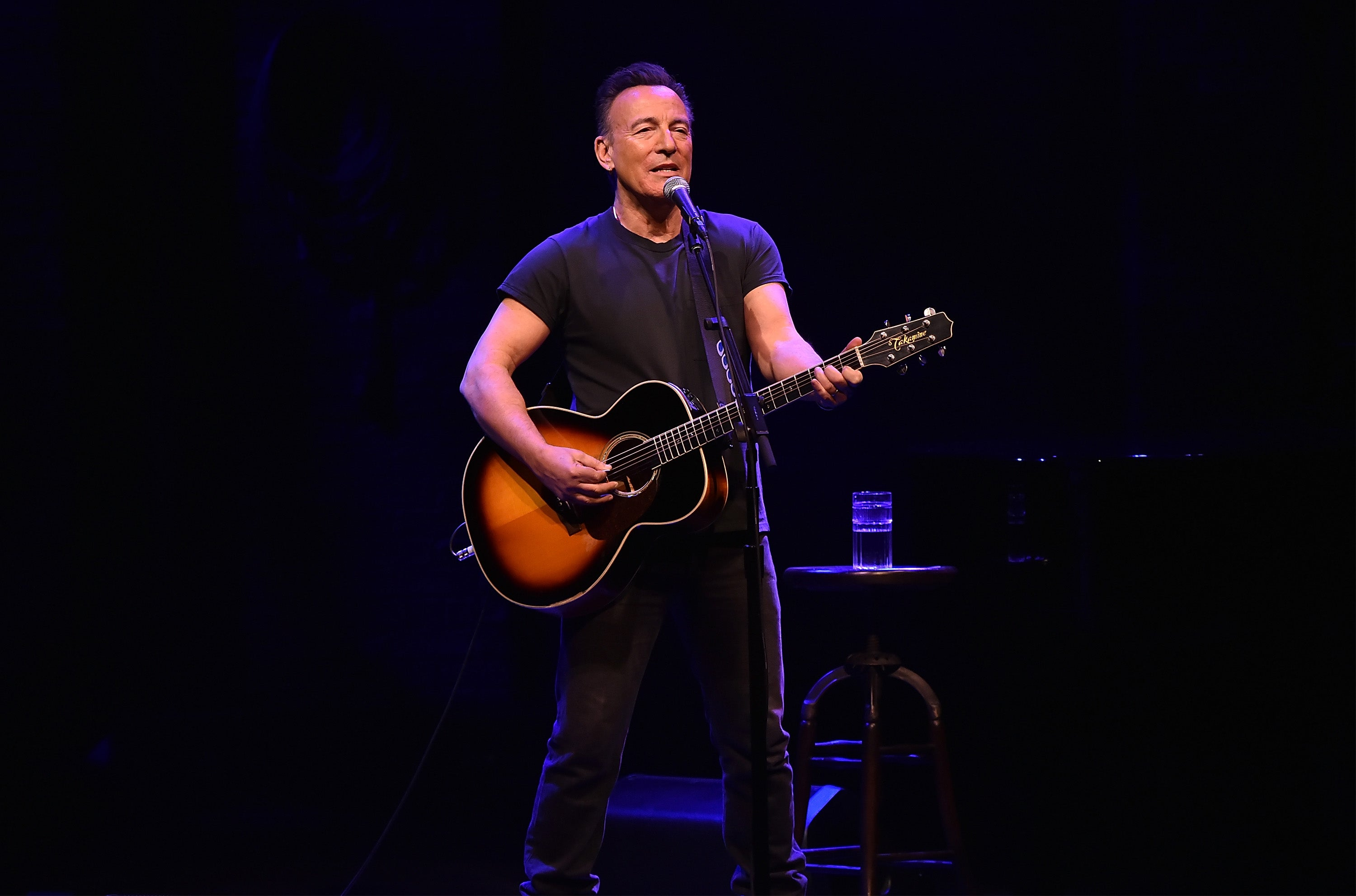 Bruce Springsteen, wearing all black, plays guitar and sings.