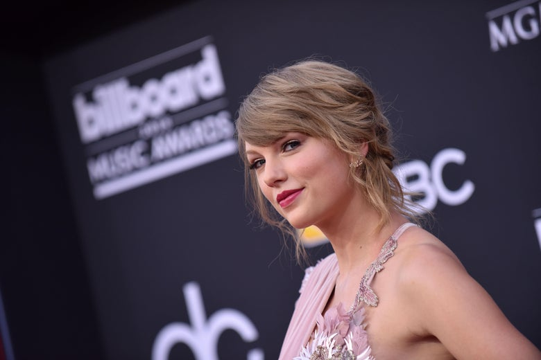 Taylor Swift on the red carpet smirks into the camera.
