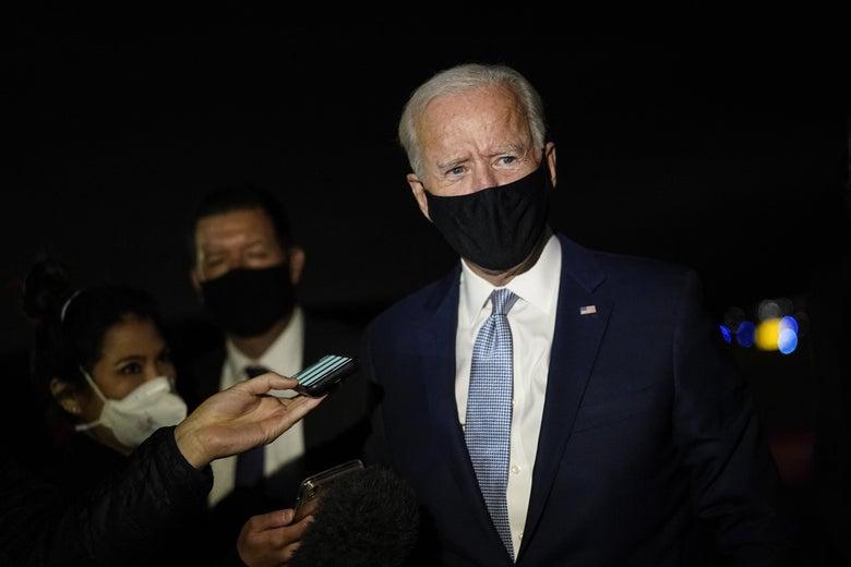 Joe Biden wearing a mask and walking by reporters