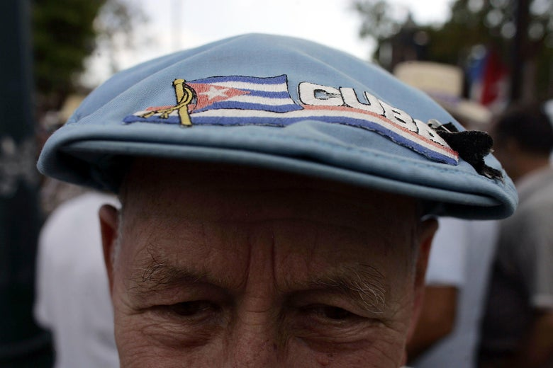 A close-up of a man's cap that says Cuba and features a Cuban flag.