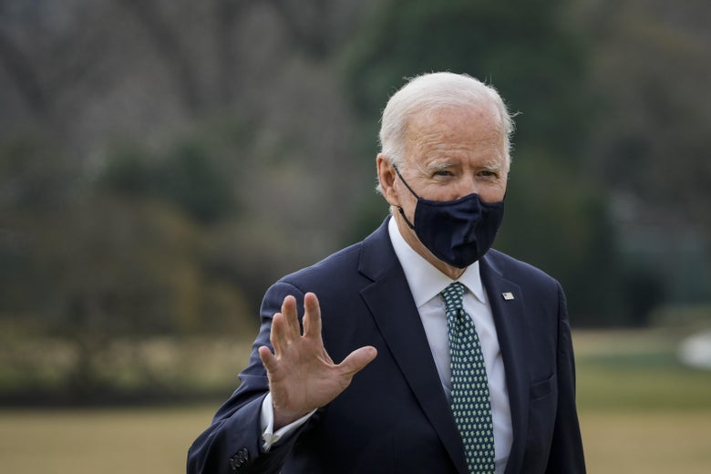 President Joe Biden waves, while wearing a face mask on the lawn.