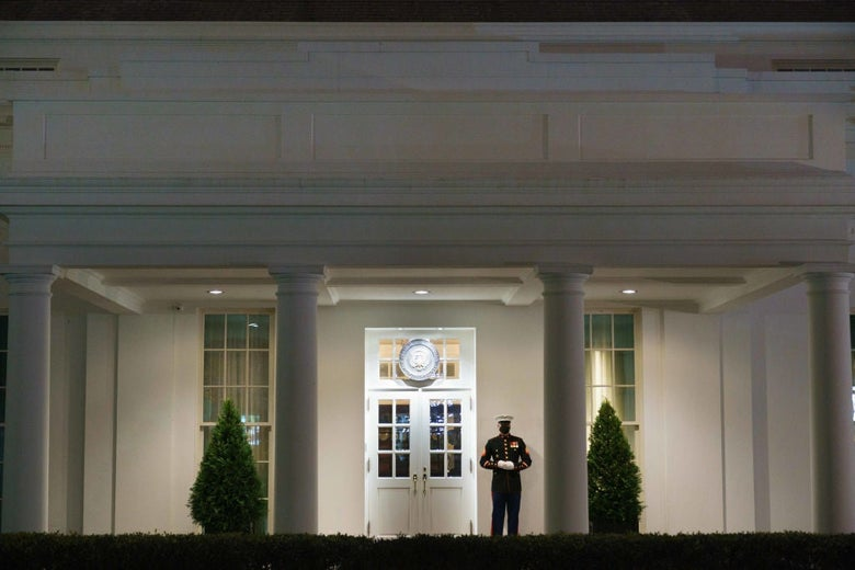 A single guard, framed by columns, stands under an awning lit against the darkness of the night.