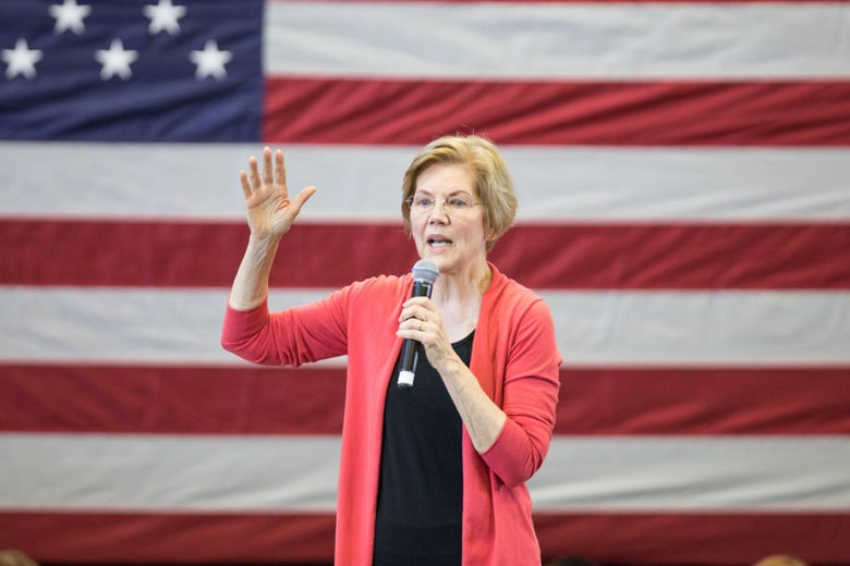 Warren speaks into a mic onstage, with an American flag behind her.