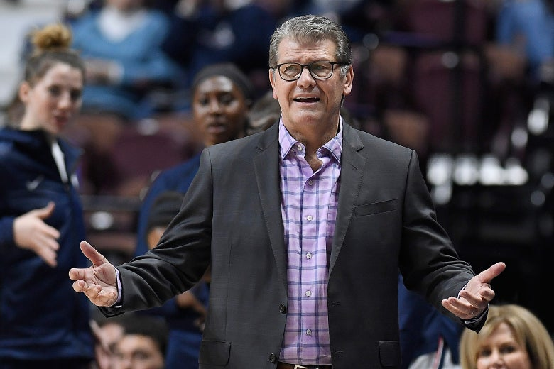 Geno Auriemma standing with his arms outstretched at a basketball game.