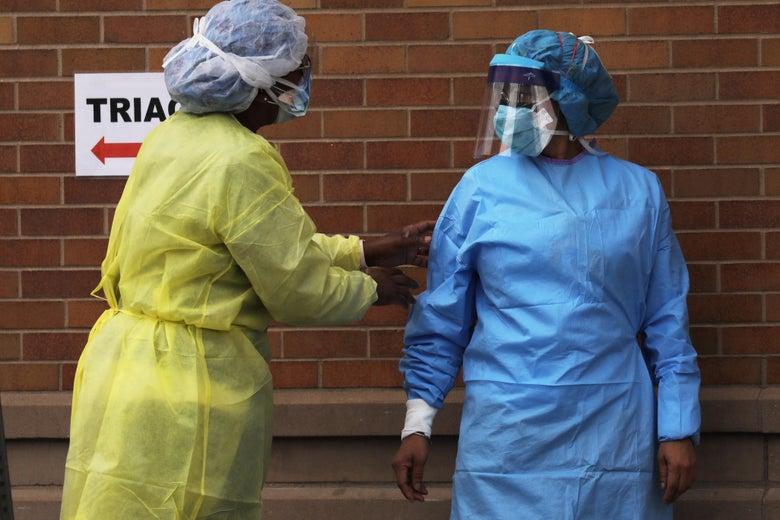 One medical worker in blue scrubs, one in yellow scrubs.