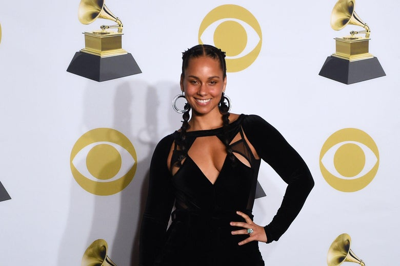 Alicia Keys poses in a long-sleeve black dress with her hair in two french braids in the press room during the 60th Annual Grammy Awards.