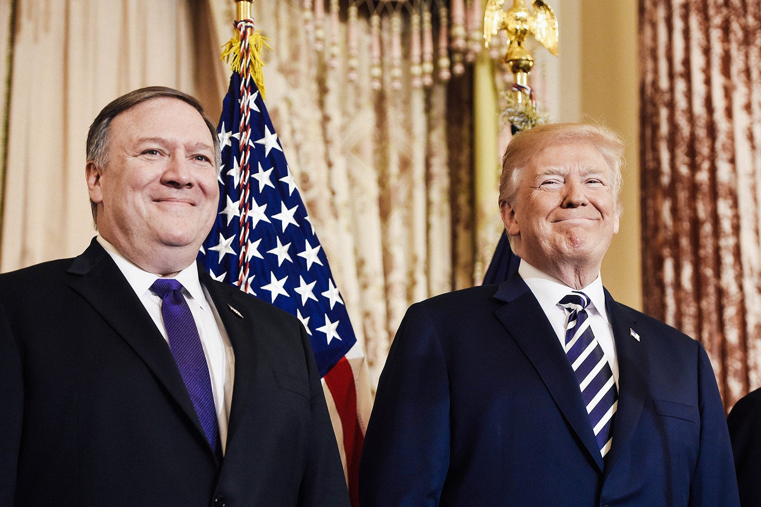 Mike Pompeo stands beside Donald Trump in an ornate room.