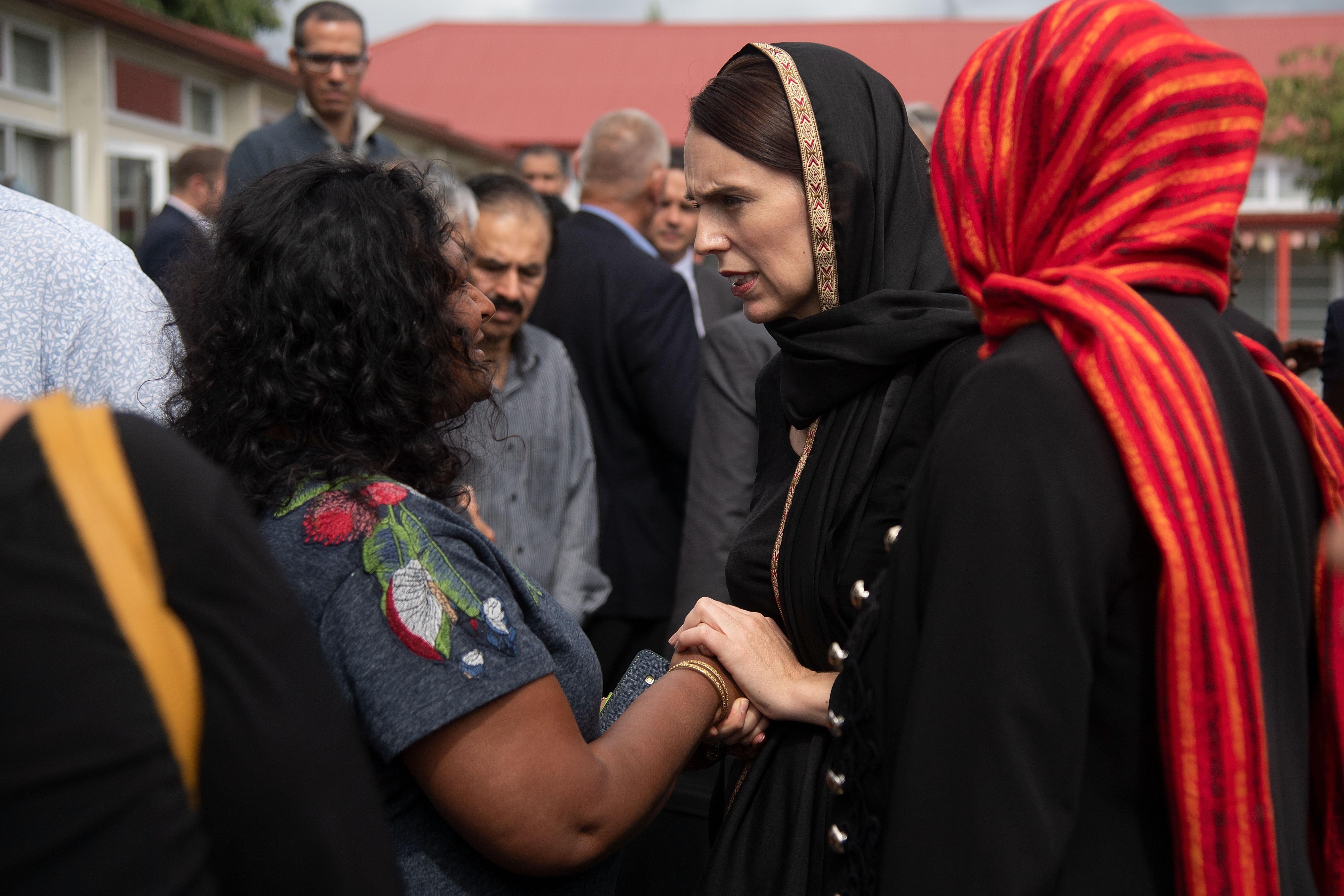 New Zealand Prime Minister Jacinda Ardern (C) speaks with a representative of the refugee centre during a visit to the Canterbury Refugee Centre in Christchurch on March 16, 2019.