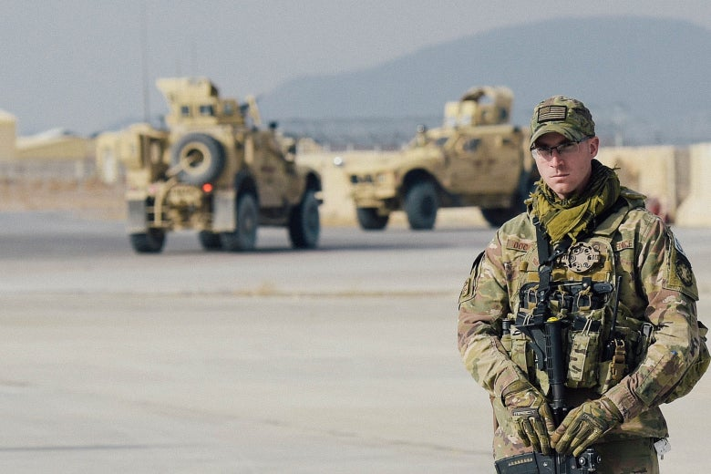 A U.S. soldier at Kandahar Air Field, with armored vehicles in the background.