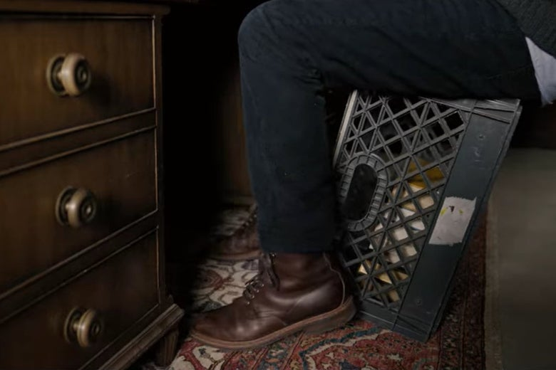 Someone sitting on a crate in front of a desk because the chair is broken.