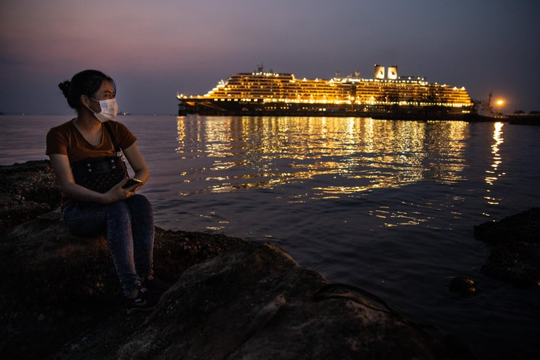 A woman with a face mask sits looking at the Westerdam cruise ship docked nearby.
