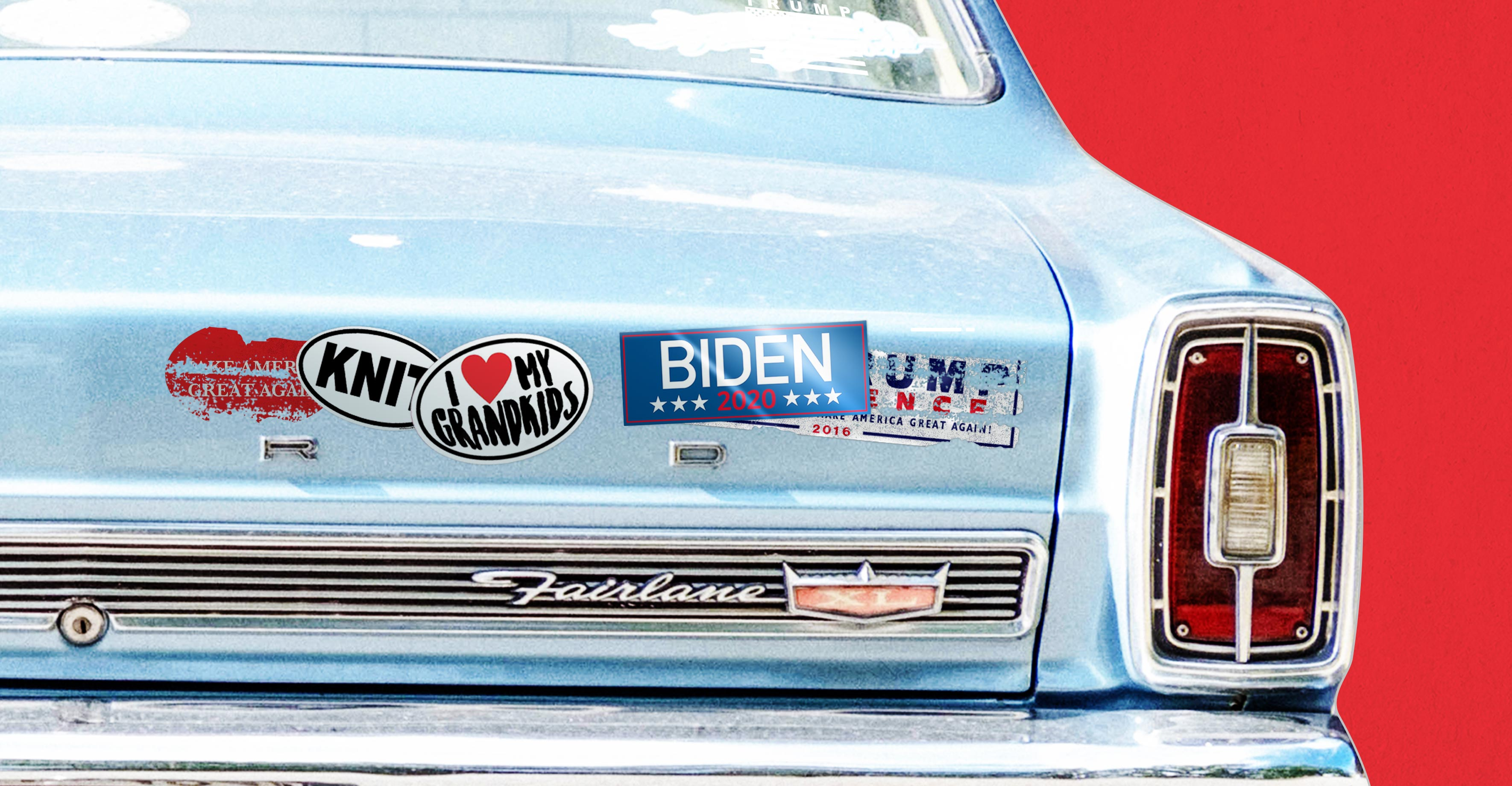 Bumper of a midcentury car covered in knitting and grandparent stickers, scratched-off Trump stickers, and one shiny Biden 2020 sticker