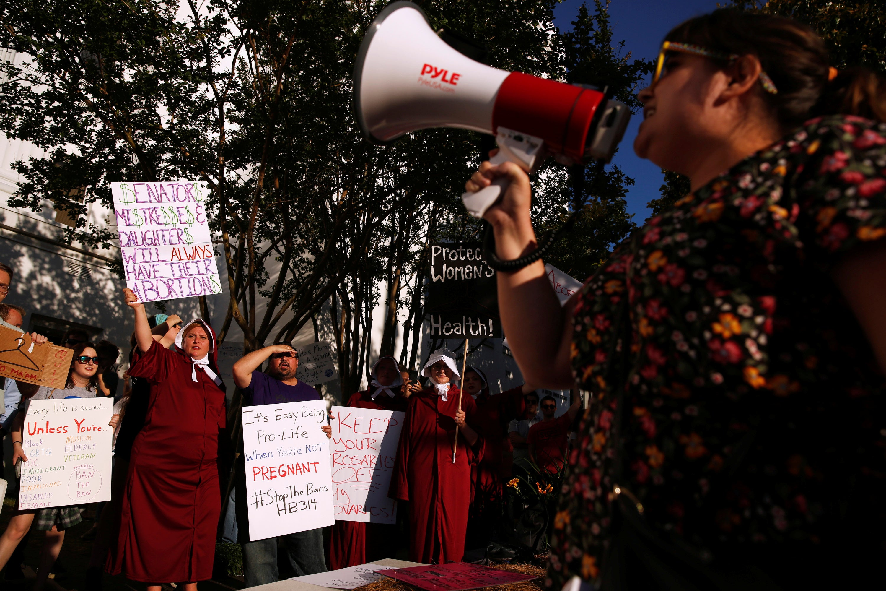 Protesters carry pro-choice signs; some are wearing red Handmaid's Tale dresses. In the foreground, a protester shouts into a megaphone.
