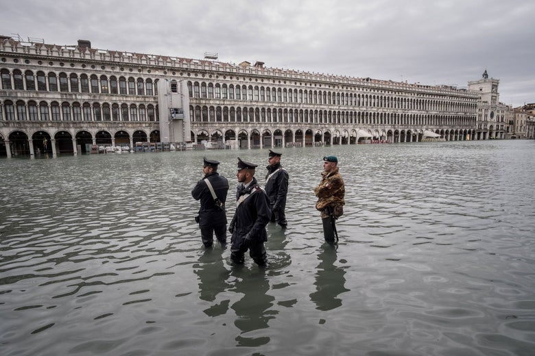 Four law enforcement agents patrol a flooded St. Mark's Square, Nov 17th 2019, Venice. The water reaches their knees.