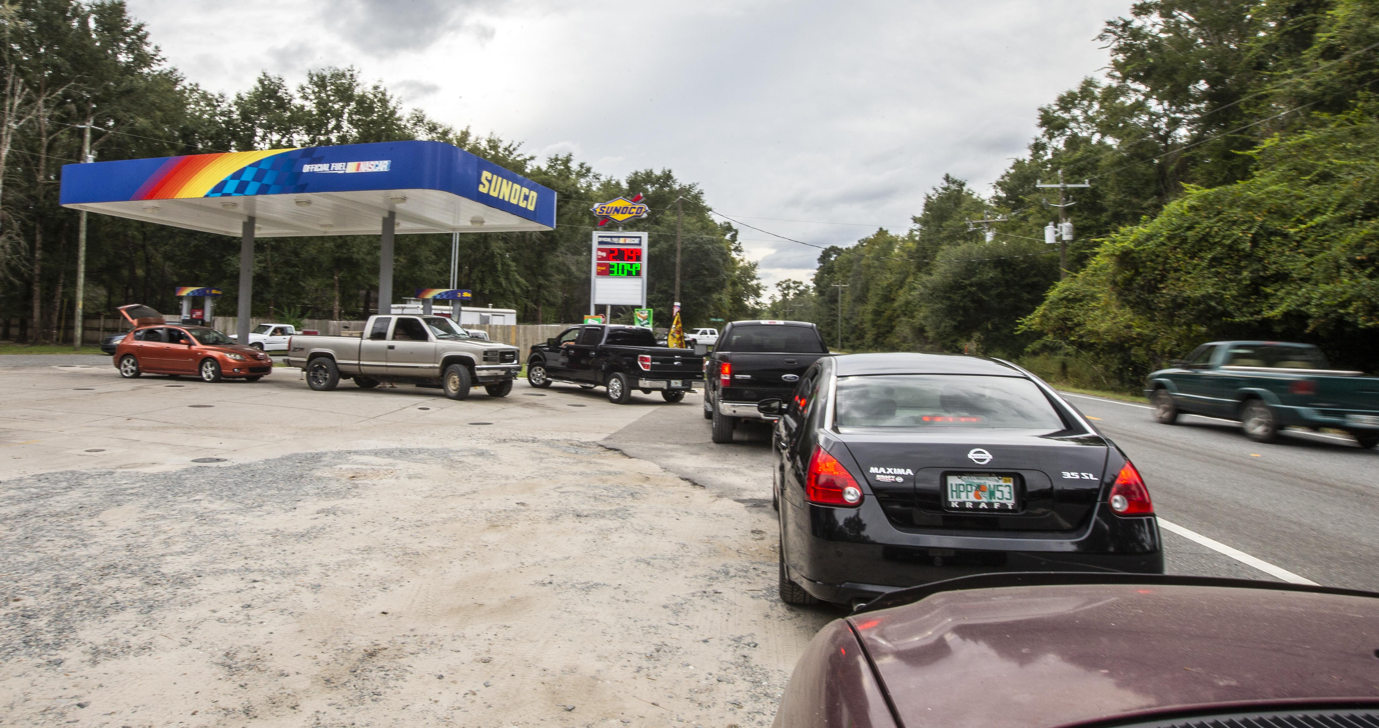 A line of cars leads up to a gas station on the side of a rural road