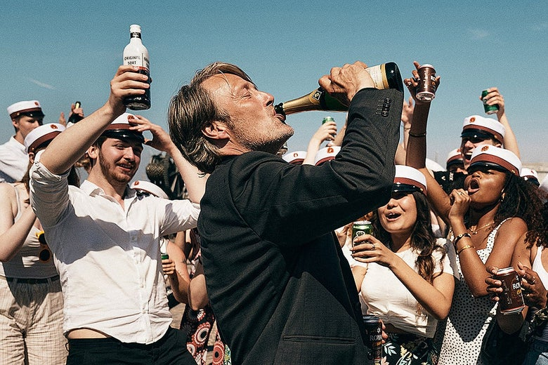 Mads Mikkelsen drinks from a bottle as a crowd cheers him on.
