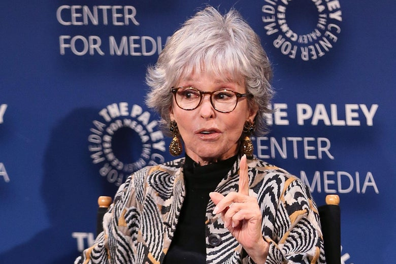 Rita Moreno sitting on a stage.