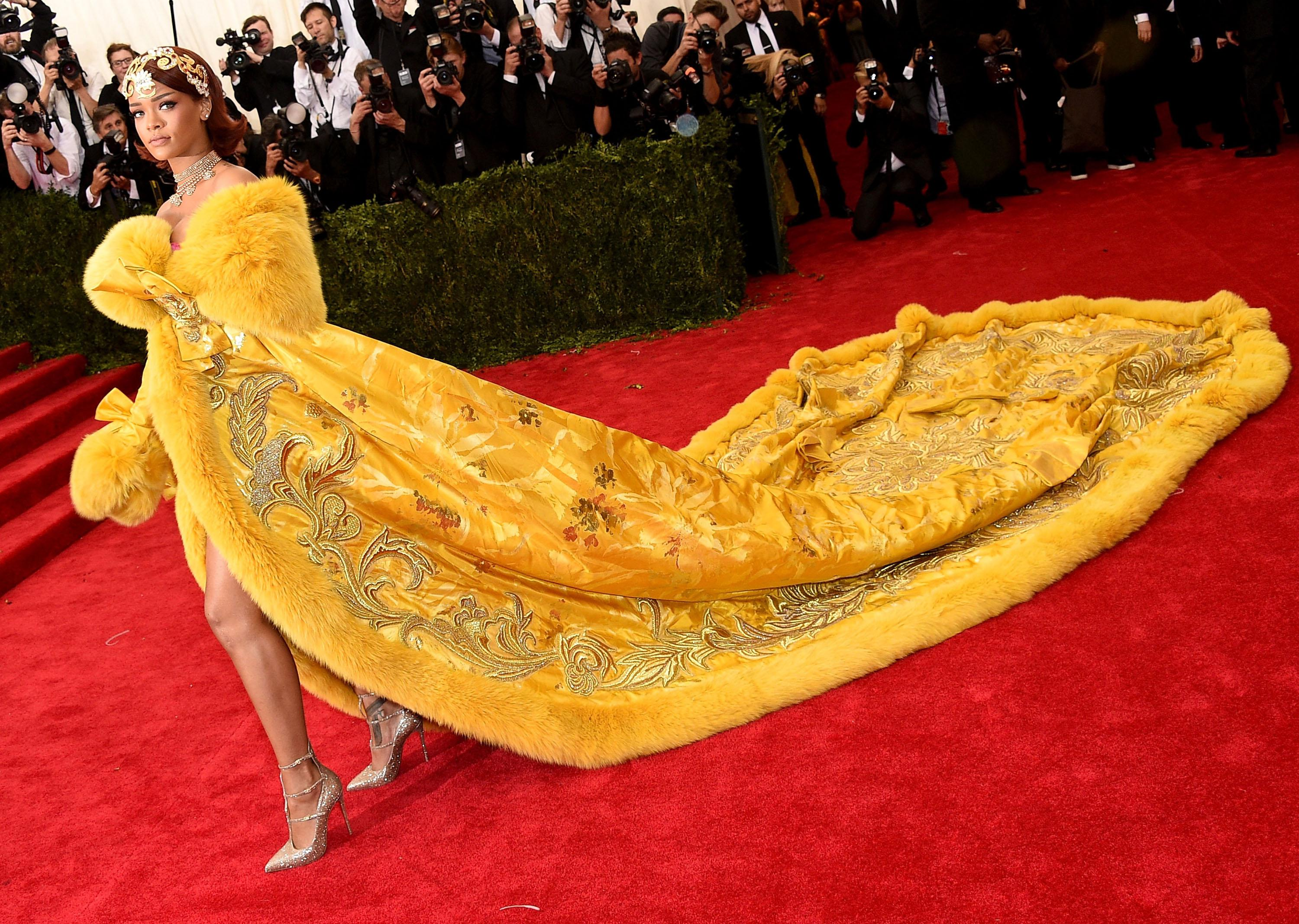 Rihanna wears a yellow dress with an enormous train.
