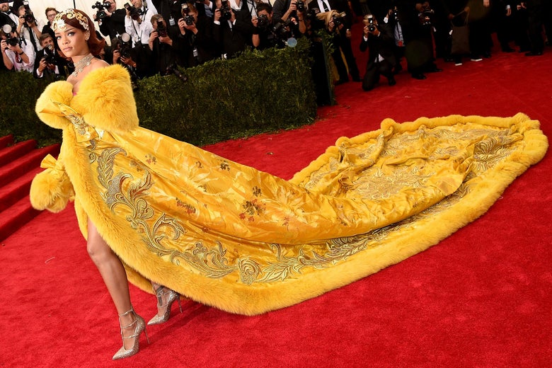 Rihanna wears a yellow dress with an enormous train.