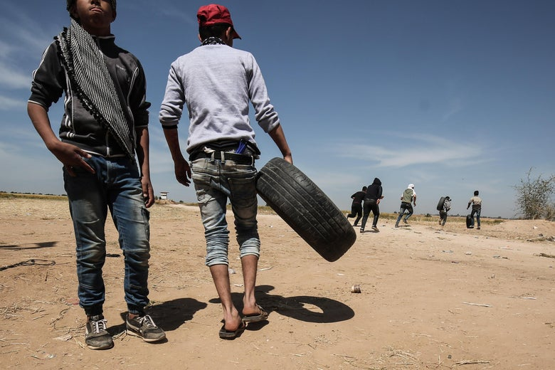 Palestinian protesters run for cover.