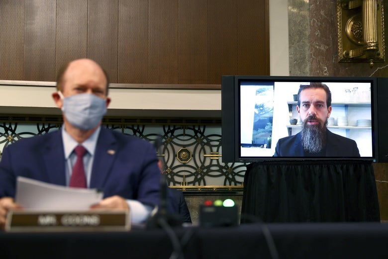 On the left, an out-of-focus man sitting behind a nameplate; on the right, a man with a beard appears on a TV screen.
