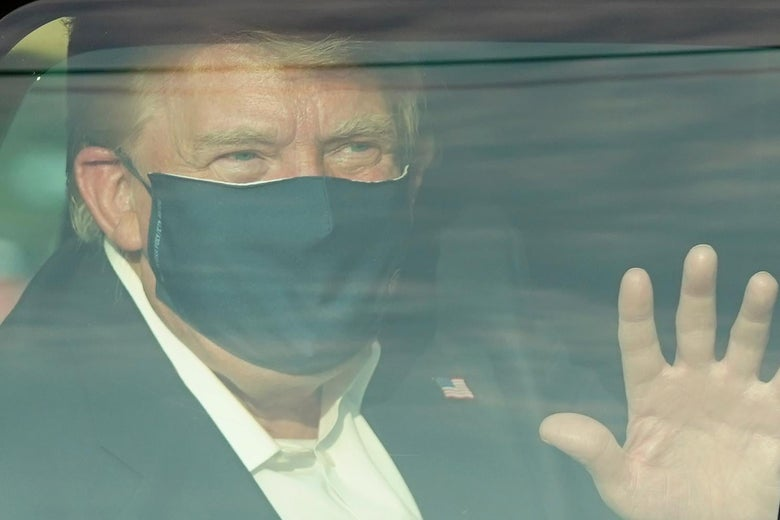 Trump, wearing a mask, waves from the back seat of a car.