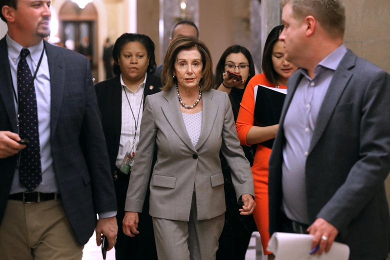 Speaker of the House Nancy Pelosi walks through the Capitol surrounded by people.