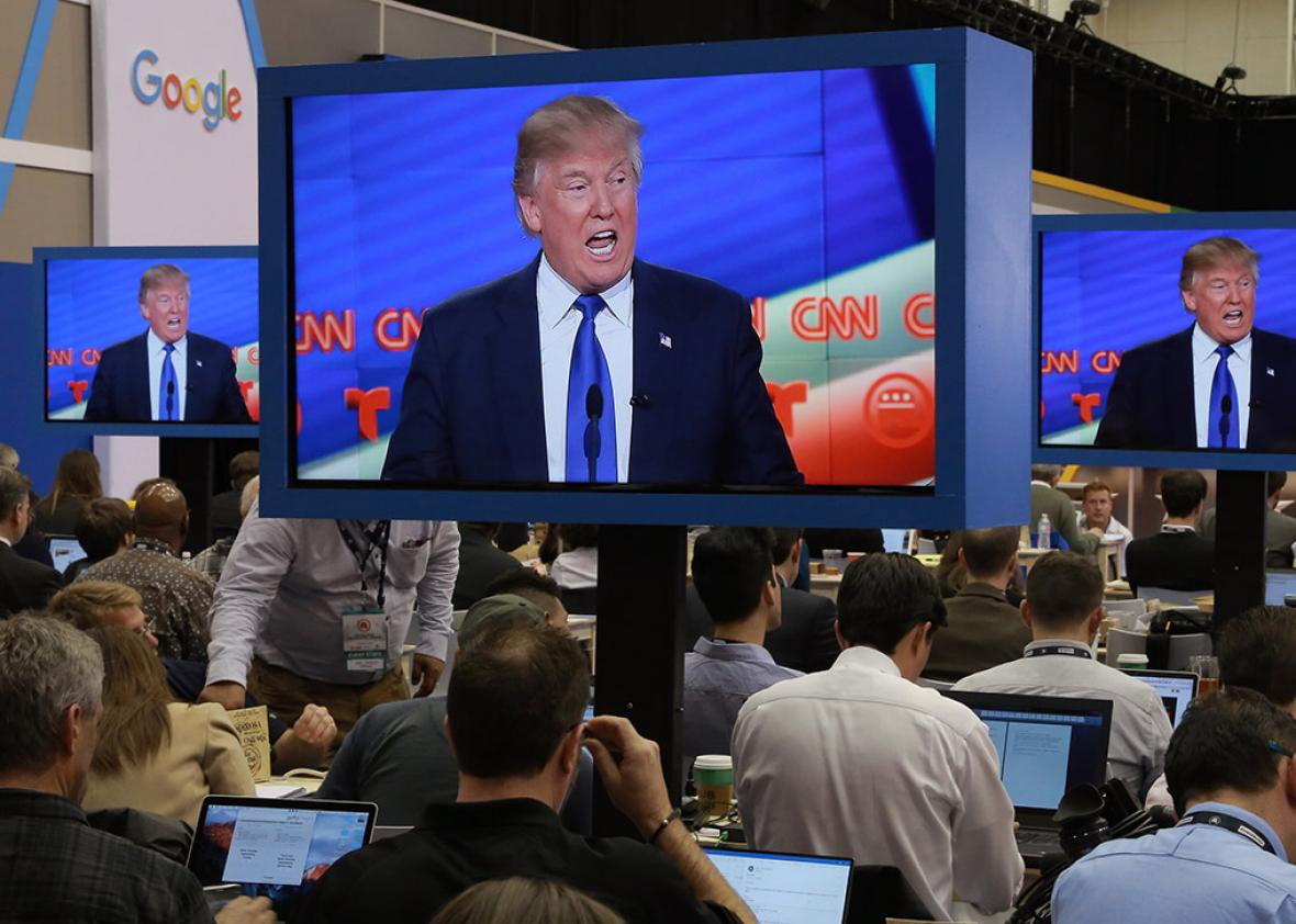 Journalists in the media filing center watch as Republican U.S. presidential candidate Donald Trump is seen speaking on television monitors during the debate sponsored by CNN for the 2016 Republican U.S. presidential candidates in Houston, Texas on Feb. 25.