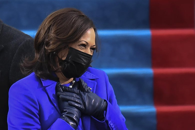 Harris smizes, wearing a black mask and clutching her gloved hands to her chest
