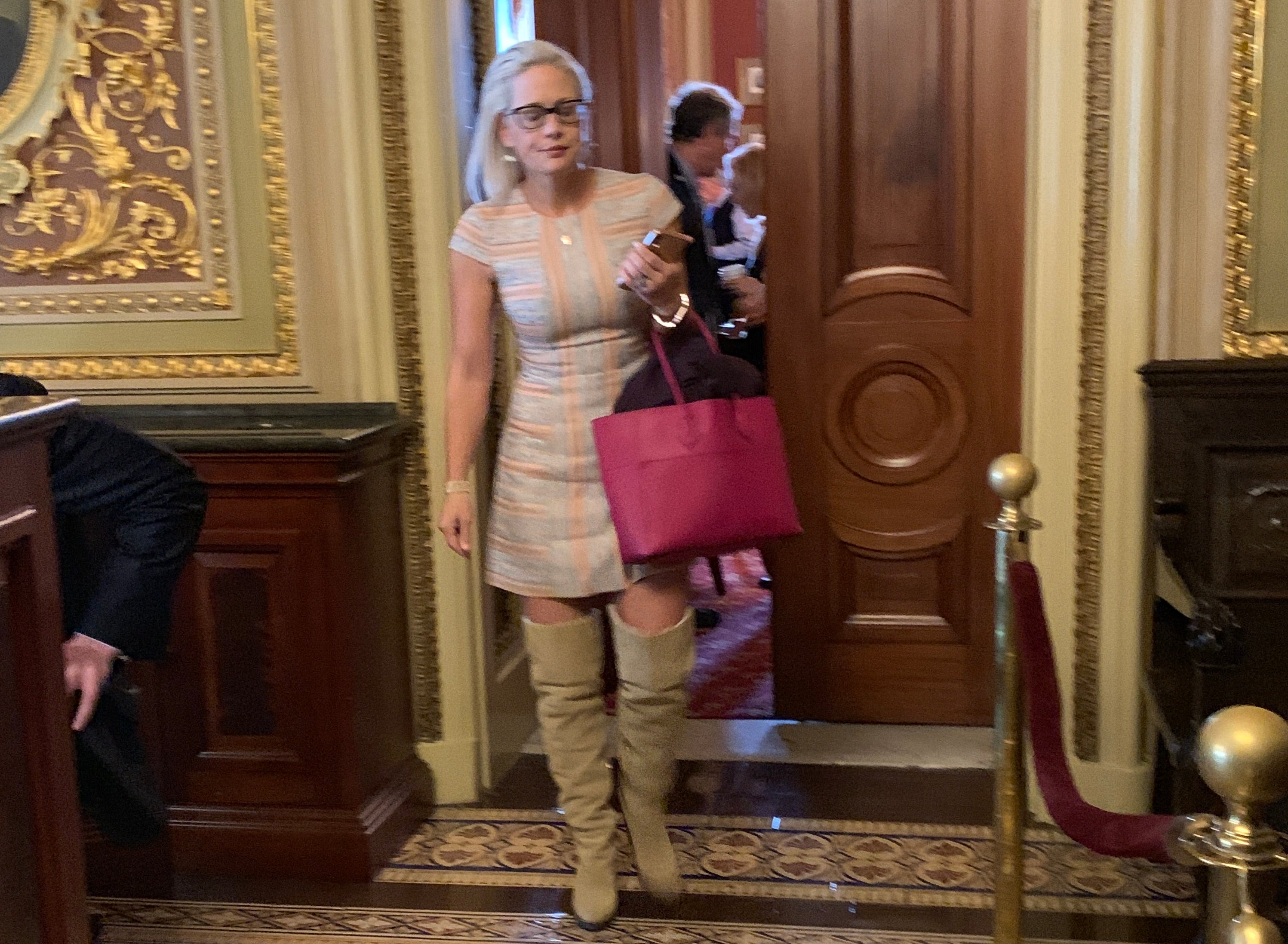 Kyrsten Sinema in a pastel striped minidress, a hot pink tote, and taupe over-the-knee boots.