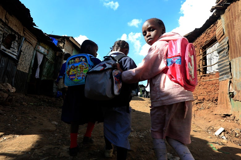 Girls wear backpacks as they walk through a street in a slum.