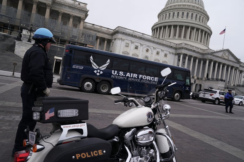 A blue U.S. Air Force bus in front of the Capitol. A police officer stands by his motorcycle in the foreground.