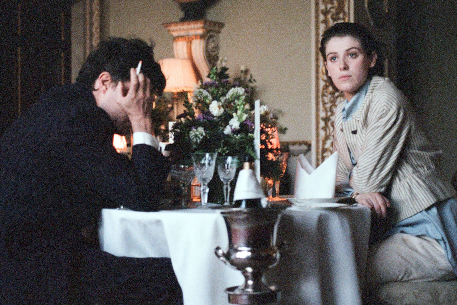 Tom Burke and Honor Swinton-Byrne dine at a fancy establishment in The Souvenir.