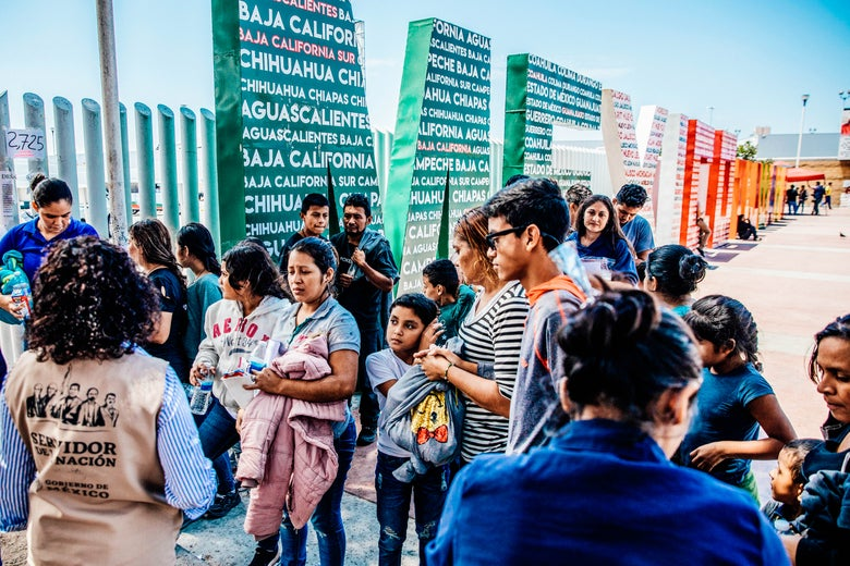 Central American migrants near a colorful sign that says MEXICO.