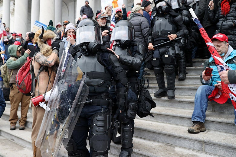 A chaotic scene on the steps of the U.S. Capitol with police officers in tactical gear facing off against a large group of rioters.