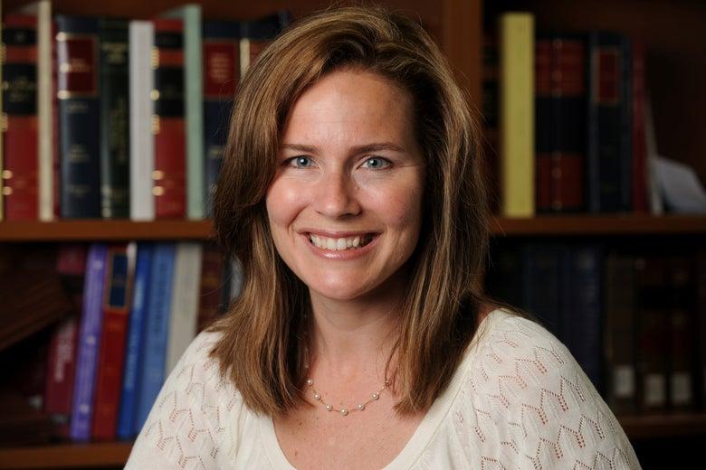 A smiling headshot of Amy Coney Barrett taken in a law office.